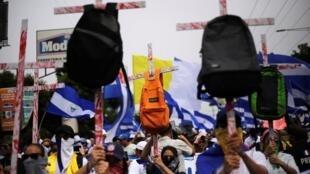 Los manifestantes sostienen cruces con mochilas durante una marcha para exigir la expulsión del presidente de Nicaragua, Daniel Ortega, en Managua, Nicaragua, el 23 de julio de 2018.