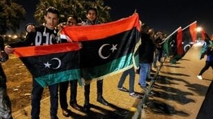 Libyans hold their national flags during a celebration marking the seventh anniversary of the revolution which toppled and killed veteran strongman Moamer Kadhafi in the eastern city of Benghazi on February 17, 2018