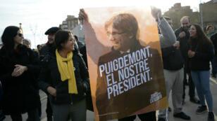 Un manifestant montre un poster à l'effigie de l'indépendantiste Carles Puigdemont lors d'une manifestation demandant sa libération à Barcelone, le 27 mars 2018.