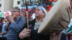 Una pareja de mapuches mientras toca un instrumento tradicional durante la protesta que se llevó a cabo el 15 de noviembre de 2018 en la ciudad de Santiago de Chile, Chile