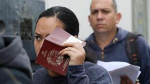 Una migrante venezolana aguarda hace fila para obtener un permiso de residencia temporal en la oficina de inmigración con su pasaporte en la mano, en Lima, Perú, el 24 de agosto de 2018.