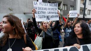 """Los manifestantes a favor del aborto sostienen una pancarta que dice """"La mujer decide, la sociedad respeta, el estado garantiza, la iglesia no interviene"""", durante un mitin contra el gobierno en Santiago de Chile, 26 de marzo de 2018."""