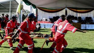 Las personas lesionadas son evacuadas después de una explosión en el estadio de Bulawayo donde el presidente de Zimbabue acaba de pronunciar un mitin el 23 de junio de 2018.