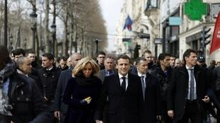 French President Emmanuel Macron and First Lady Brigitte Macron walk down the Champs Elysees Avenue March 9, 2020. REUTERS OK