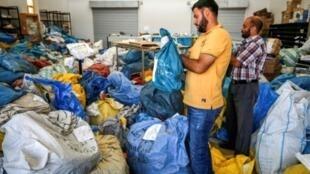 عمال فلسطينيون بمقر البريد الفلسطيني في أريحا يفرزون أطنانا من البريد الذي أفرجت عنه إسرائيل بعد سنوات، 14 أغسطس 2018
