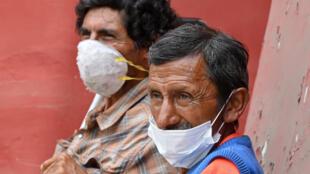 شخصان بلا مأوى صورا في 31 مارس/آذار 2020 قرب مركز إيواء تم توفيره بالعاصمة ليما في بيرو بعد جائحة فيروس كورونا.