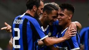 El delantero del Inter Lautaro Martínez (c) recibe las felicitaciones de sus compañeros por un gol marcado al Torino en un partido de la Serie A italiana el 13 de julio de 2020 en Milán