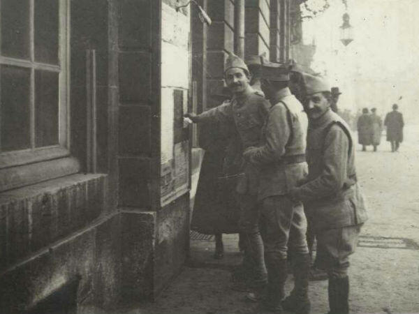 Soldiers in front of a poster announcing the armistice in Nancy