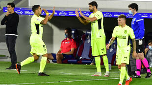 المهاجم الاوروغوياني لأتلتيكو مدريد لويس سواريس (يسار) يترك مكانه لدييغو كوستا (يسار) في المباراة ضد هويسكا في الدوري الإسباني في 30 أيلول/سبتمبر 2020.