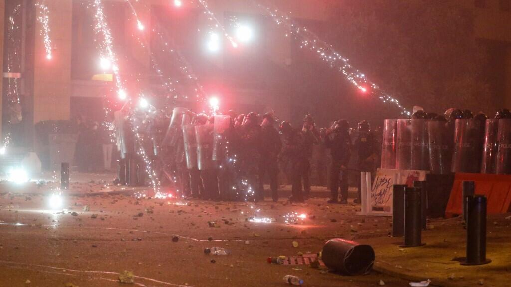 Se disparan fuegos artificiales frente a los agentes de policía que se colocan detrás de los escudos antidisturbios durante una protesta contra una élite gobernante acusada de dirigir al Líbano hacia la crisis económica en Beirut, Líbano, 18 de enero de 2020.