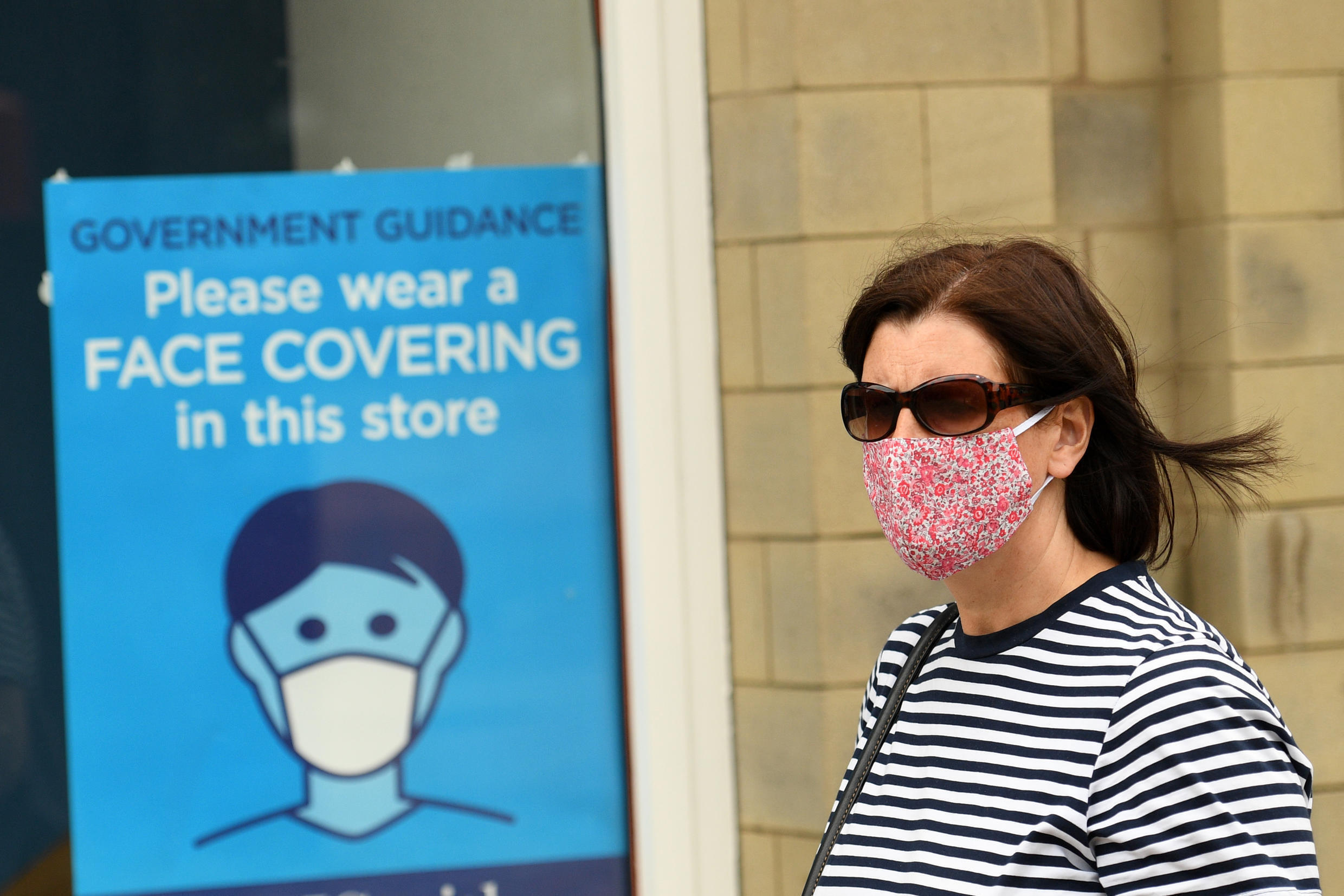 A woman wearing a protective face covering as a precaution against the transmission of the novel coronavirus passes a sign advising shoppers of the need to wear a face covering in Halifax, England, on August 9, 2020.
