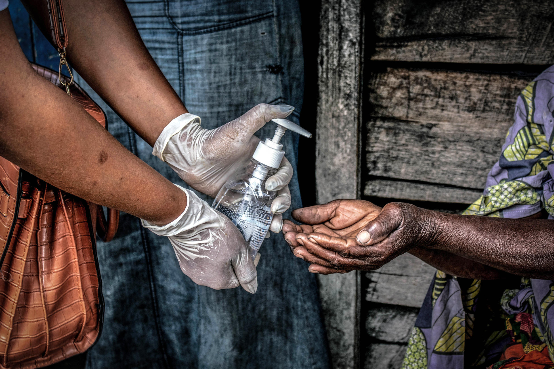 En avril 2020, trois jours après le premier cas de Covid-19 en RD Congo, une femme distribue du gel désinfectant à Goma, alors que les ressources en eau sont peu accessibles.