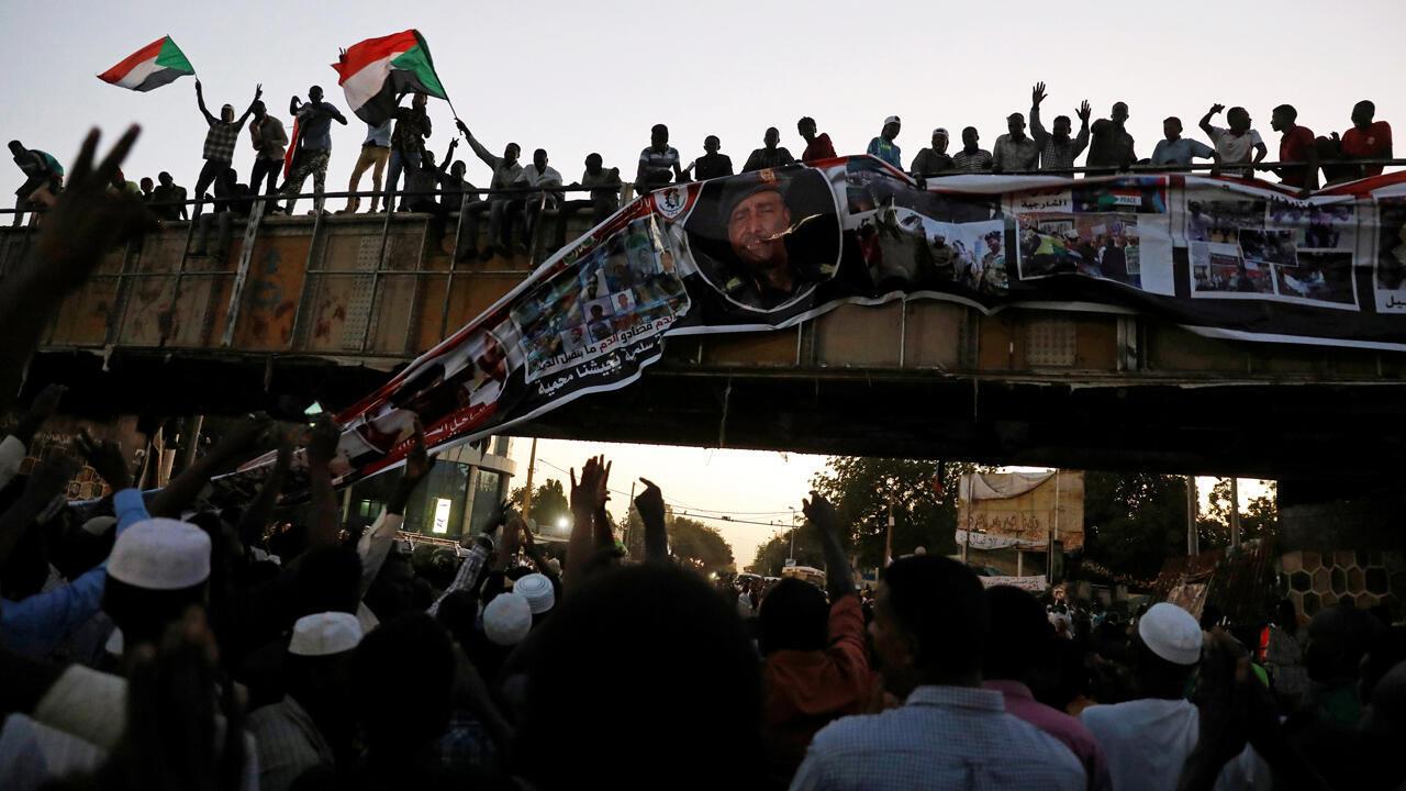 Un manifestante grita con un megáfono mientras otros sostienen banderas y pancartas durante las protestas contra el gobierno en Argel, Argelia, el 23 de abril de 2019.