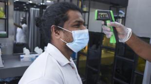 مصفف شعر هندي يقيس حرارة أحد زملائه في دبي في 5 أيار/مايو 2020
