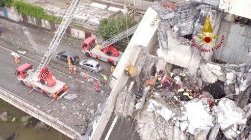 Photo prise et diffusée par le service d'incendie et de secours italien, le 15 août 2018 montrant des sauveteurs au travail dans les décombres après l'effondrement du pont.