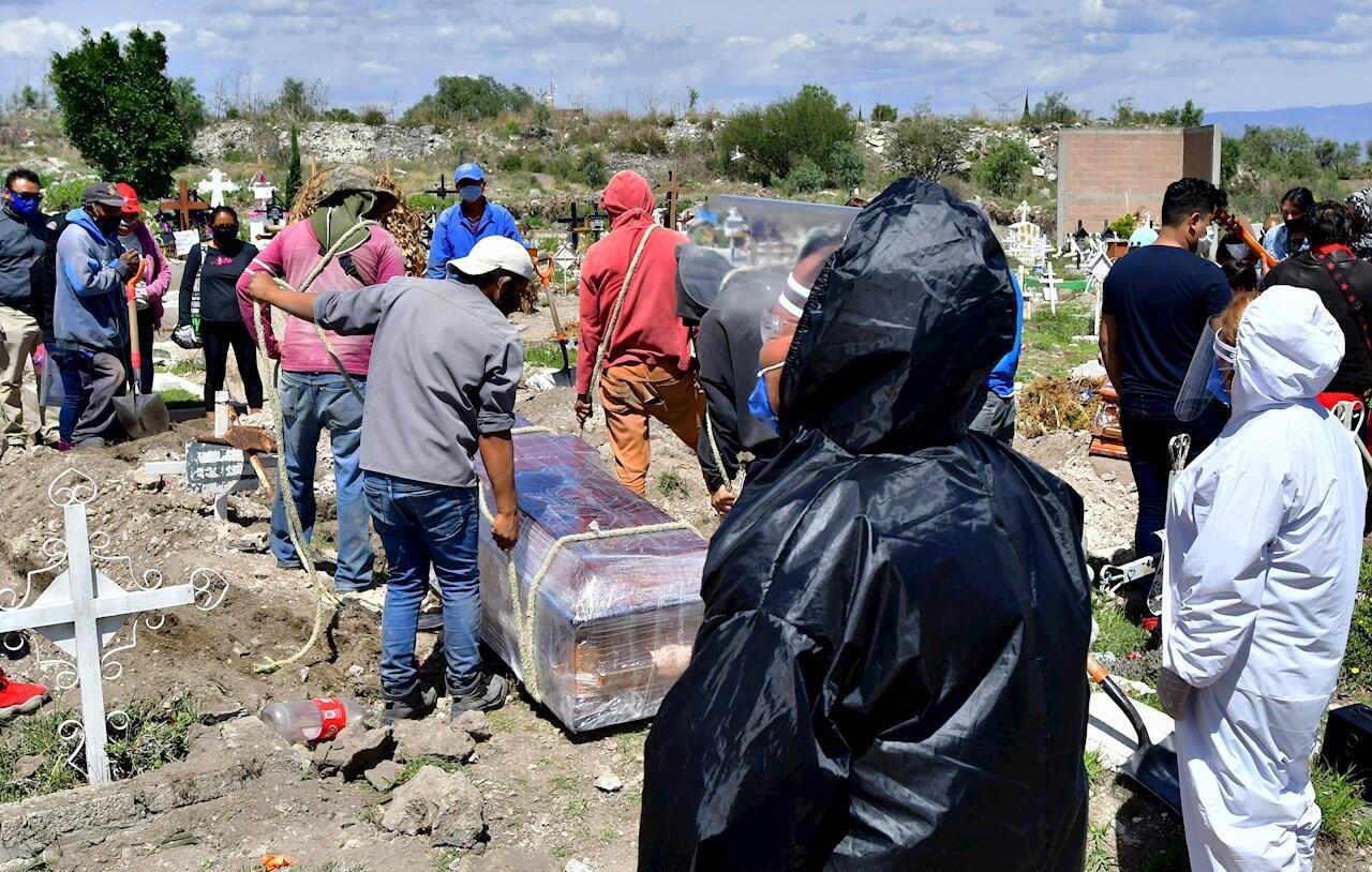 Trabajadores municipales introducen en una fosa un féretro, en el panteón de San Isidro, en el municipio de Ecatepec, México, el 2 de julio de 2020.