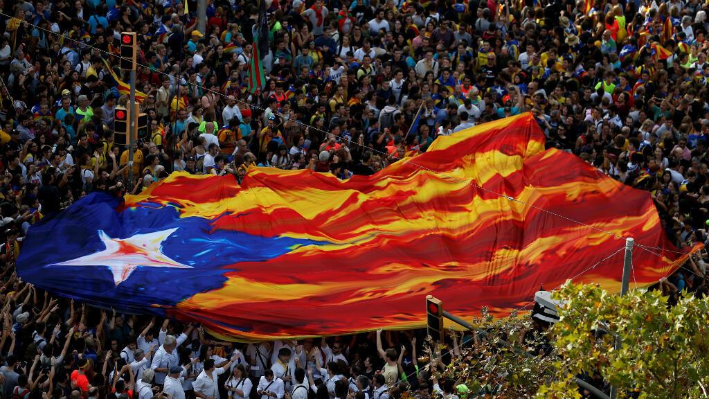 Manifestantes catalanes se reúnen en la avenida Paseo de Gracia durante la huelga general de Cataluña con una 'estelada', bandera símbolo del independentismo catalán. Barcelona, España, el 18 de octubre de 2019.