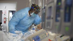 ممرضة إلى جانب مريض في قسم المصابين بكوفيد-19 في مستشفى في هيوستن في الولايات المتحدة في 4 كانون الأول/ديسمبر 2020