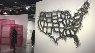 """A woman stands next to a piece by Teresita Fernandez, """"Untitled (Specter),"""" representing a US map made of charcoal pins as a metaphor of the trace left by minorities"""