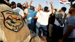 عنصر من قوات مكافحة الشغب العراقية يقف بالقرب من متظاهرين في مدينة البصرة في 13 تموز/يوليو 2018