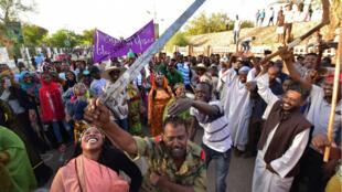 Un soldat soudanais se joint à un groupe de danse traditionnelle pour célébrer la chute du président Omar el-Béchir, non loin du quartier général de l'armée à Khartoum, le 15avril2019.