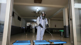 A worker wearing a protective suit disinfects a bus station, following the outbreak of coronavirus disease (COVID-19), in Algiers, Algeria March 16, 2020.