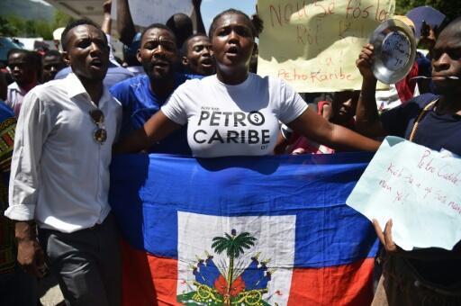 Manifestantes cantan y levantan pancartas en una protesta para denunciar corrupción en el manejo de miles de millones de dólares del programa venezolano PetroCaribe de suministro preferencial de crudo, en Puerto Príncipe, el 24 de agosto de 2018.