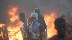 Manifestantes caminan junto a las barricadas en llamas durante una protesta, en Puerto Príncipe, Haití, el 18 de noviembre de 2018, para exigir una investigación sobre el presunto uso indebido de los fondos de PetroCaribe, programa patrocinado por Venezuela.