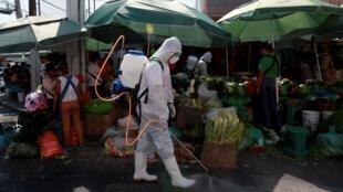 موظف محلي يقوم بتعقيم سوق شعبية في العاصمة المكسيكية، 5 مايو/أيار 2020.