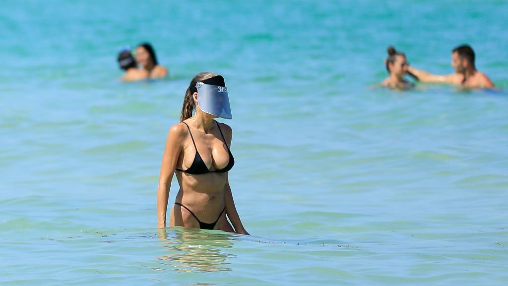 Imagen de una playa en Miami, donde una mujer se baña con una mascarilla protectora para protegerse del virus.