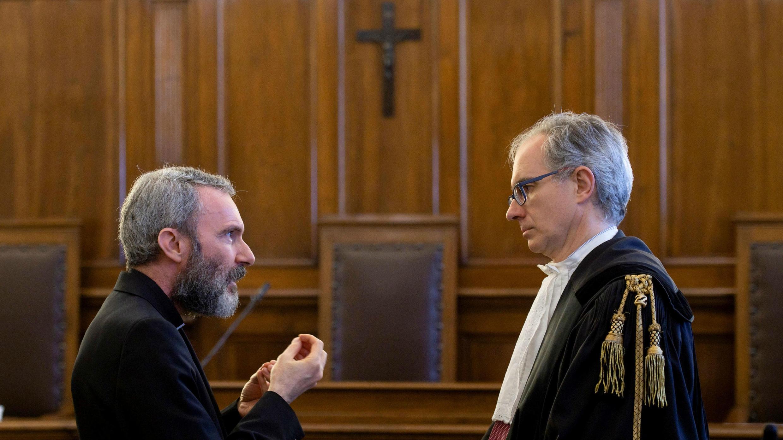 El padre Carlo Alberto Capella, un sacerdote católico sentenciado a cinco años de cárcel por posesión de pornografía infantil, habla con su abogado durante un juicio en el Vaticano el 23 de junio de 2018.