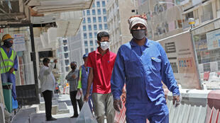 Workers wearing protective masks walk by on a street in Qatar's capital Doha