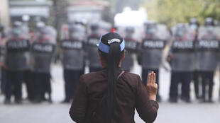 A female protester flashes the three-fingered salute in front of police in Mandalay, Myanmar, on February 20, 2021.