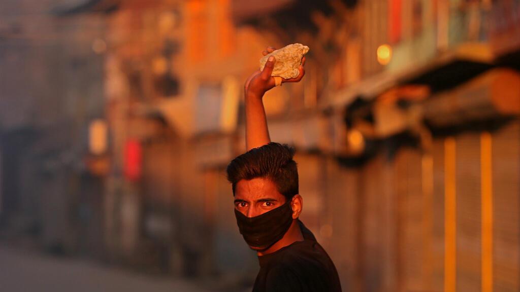 Un manifestante de Cachemira enmascarado observa mientras se prepara para tirar una piedra hacia la policía de India durante una protesta después del final de la segunda fase de las elecciones generales en Srinagar, India, el 18 de abril de 2019.