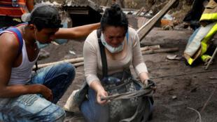 Norma Amabilia, quien busca a sus seres queridos desaparecidos tras la erupción, reacciona al encontrar una pieza de ropa de un familiar entre los escombros cerca de su casa en San Miguel Los Lotes, Guatemala el 8 de junio de 2018.