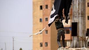 """مقاتل من قوات سوريا الديمقراطية يزيل علم تنظيم """"الدولة الإسلامية"""" في مدينة الطبقة السورية"""