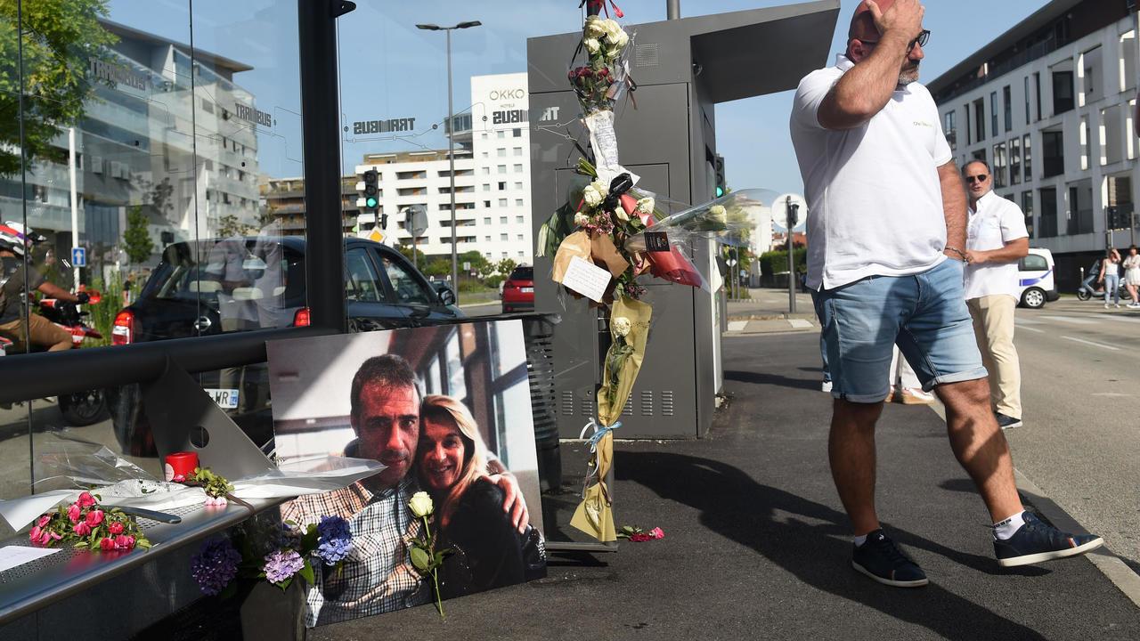 رجل يمر أمام صورة فيليب مونغيو سائق الحافلة القتيل وزوجته فيرونيك في مدينة بايون جنوب غرب فرنسا في 8 يوليو/تموز 2020.
