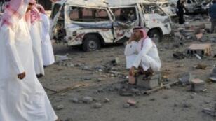 سعوديون إلى جانب حطام سيارات في مدينة نجران الحدودية السعودية بعد أسبوع من إصابتها بصاروخ أطلق من اليمن، 27 آب/أغسطس 2016