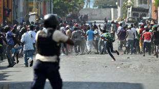 Manifestantes huyen cuando la policía haitiana abre fuego, en el centro de la capital, Puerto Príncipe, el 13 de febrero de 2019, en medio de las protestas contra el presidente Jovenel Moise y el uso indebido del fondo Petrocaribe.