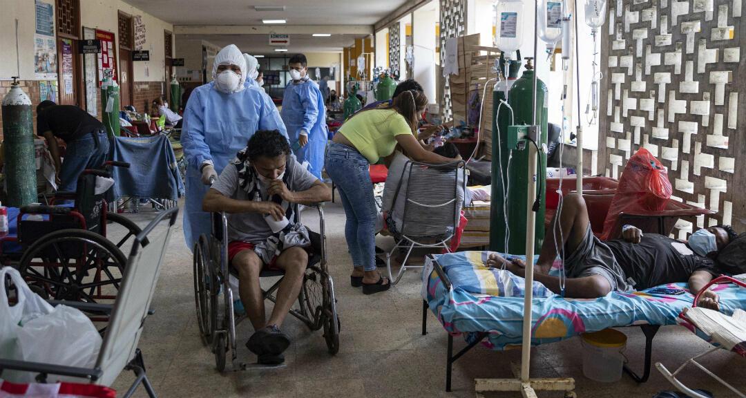 Un médico con traje de bioseguridad traslada a un paciente en silla de ruedas, en una sala con convalecientes de Covid-19 en el Hospital Regional de Iquitos, en Iquitos, Perú.