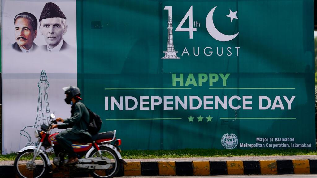 Un motociclista pasa junto a una valla publicitaria del Feliz Día de la Independencia con imágenes del líder fundador Muhammad Ali Jinnah y el poeta nacional Allama Muhammad Iqbal, exhibidas para las celebraciones del Día de la Independencia de Pakistán, en Islamabad, Pakistán, el 13 de agosto de 2020.