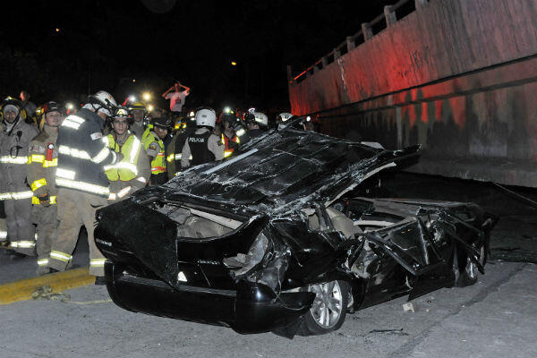 Rescue workers stand before a destroyed car after the collapse of a bridge in the city of Guayaquil