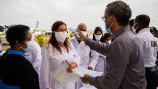 Un hombre controla la temperatura de los médicos cubanos a su llegada al aeropuerto de la isla caribeña francesa de Martinica, el 26 de junio de 2020