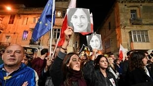 People hold placards and photos of killed journalist Daphne Caruana Galizia during a protest called for by Galizia's family and civic movements on December 3, 2019 outside the police headquarters in Valletta.
