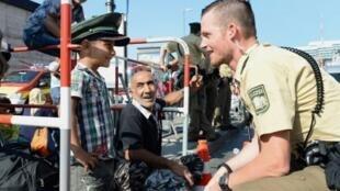 - شرطي يمازح طفلا مع وصول مهاجرين إلى ميونيخ