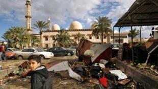 ليبيون يتفقدون موقع التفجيرين في بنغازي في 24 كانون الثاني/يناير 2018.
