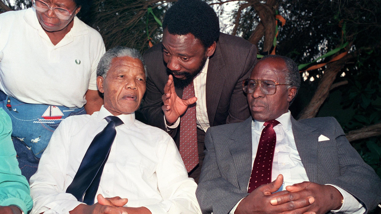 El líder antiapartheid y miembro del Congreso Nacional Africano (ANC) Nelson Mandela (L) y el ex preso político Andrew Mlangeni (R) escuchan a Cyril Ramaphosa del Comité de Recepción sobre cómo dispersar a la gran multitud que se había reunido fuera de su casa de Soweto, febrero 13