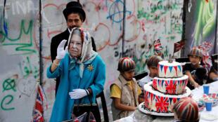 Una persona disfrazada de reina Isabel durante la celebración realizada por el artista inglés Banksy.