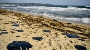 Pools of tar fester on the sand of Pampelone beach in Ramatuelle, in the Gulf of Saint-Tropez