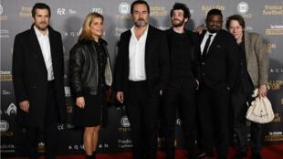 """L'équipe du film """"Le Grand bain"""", selectionnée dans dix catégories, entoure son réalisateur Gilles Lellouche au Grand Palais, à Paris, le 3 décembre 2018."""